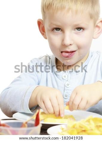 Happy childhood. Boy child kid preschooler eating peeled apple fruit or making batter for drop scones. At home. - stock photo