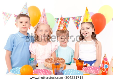 Happy childhood. Group of funny little children standing at adorned table with birthday cake on it during party.