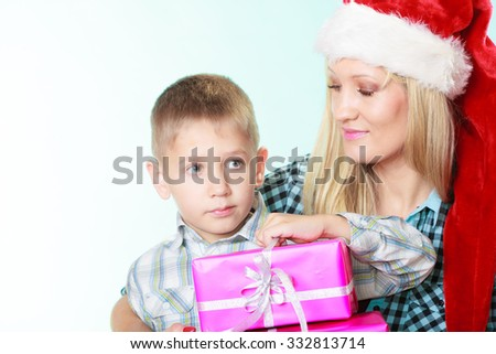 Happy childhood, holidays christmas time. Mother in santa claus hat and little boy child with stack of pink presents gift boxes on blue
