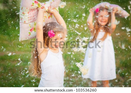 Happy childhood:little girls having fun with pillows outdoor - stock photo