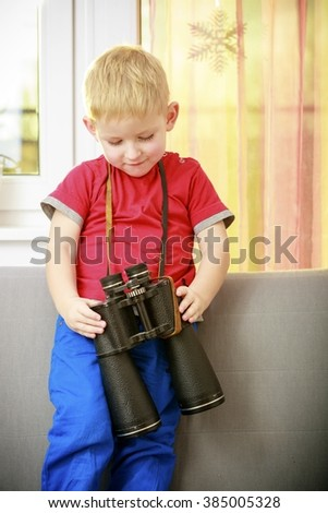 Happy childhood. Portrait of boy child kid preschooler playing with binoculars. At home. Real.