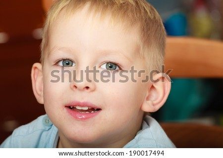 Happy childhood. Portrait of happy smiling blond boy child kid preschooler sitting on chair. Indoor.