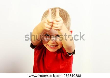 Happy childhood. Portrait of smiling funny blond boy child kid preschooler showing thumb up success hand sign gesture. Indoor. - stock photo