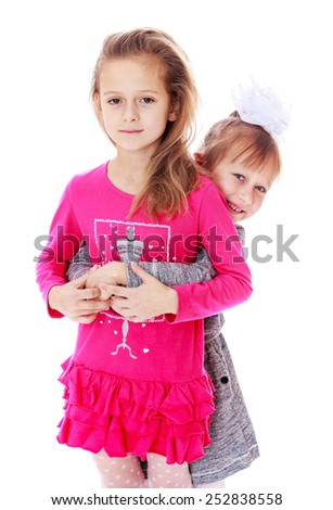 Happy childhood, the family concept.Charming girl sisters smiling cheerfully. Isolated on white. - stock photo