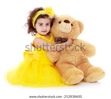 Happy childhood, the family concept.Cheerful caucasian girl in a yellow dress and a bear in his hands.Isolated on white. - stock photo