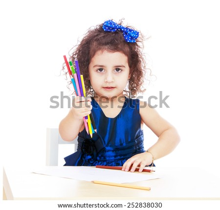 Happy childhood, the family concept.Close-up of a girl sitting at the table and shows pencils.Isolated on white. - stock photo