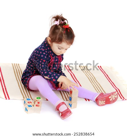 Happy childhood, the family concept.Cute little girl puts cubes sitting on the carpet.Isolated on white. - stock photo