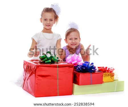 Happy childhood, the family concept. Cute little sisters with lots of gifts.Isolated on white. - stock photo