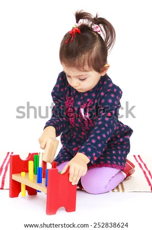 Happy childhood, the family concept.Very busy little girl hammering.Isolated on white. - stock photo