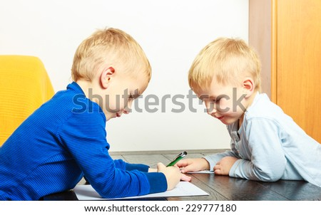 Happy childhood. Two blond boys children kids brothers with pen writing drawing on paper doing homework. At home. - stock photo