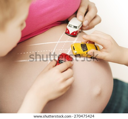 Happy childplaying next to belly of pregnant woman - stock photo