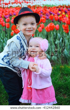 Happy children against spring flowers background. Sister and brother hug on a background of field of blooming tulips in Amsterdam region, Holland, Netherlands.  - stock photo