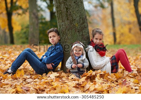 happy children among the leaves in autumn park