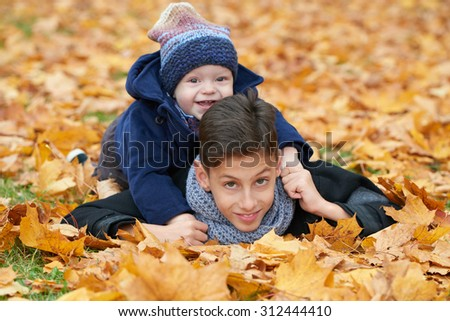 happy children among the leaves in autumn park - stock photo