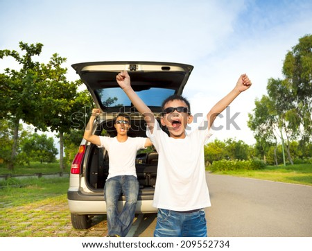 happy children and father raise arms with their car  - stock photo