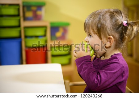 Happy children and healthy food, baby girl eating fruit at school - stock photo