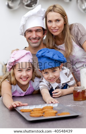 Happy children and parents eating cookies after baking in the kitchen - stock photo