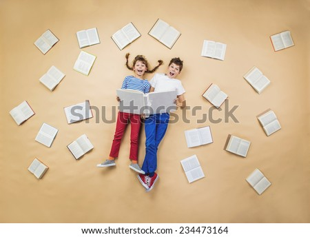 Happy children are reading book on the floor with group of books around them - stock photo