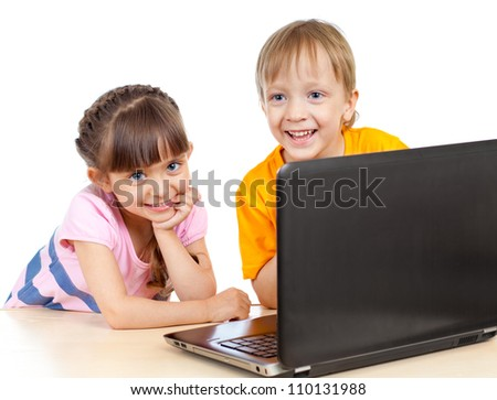 happy children boy and girl using a laptop - stock photo
