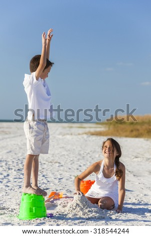 Happy children, boy girl, brother and sister having fun playing in the sand on a beach with bucket and spade - stock photo