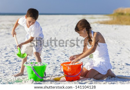 Happy children, boy & girl, brother& sister having fun playing in the sand on a beach with bucket and spade - stock photo