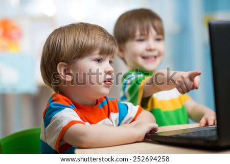 happy children boys looking at laptop at home