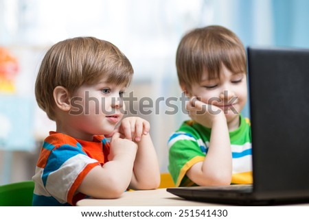 happy children boys looking at laptop indoors - stock photo