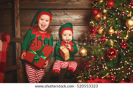 happy children brother and sister  elf, helper of Santa with a Christmas gifts
