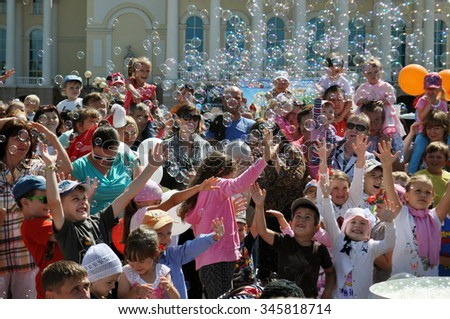 Happy children catch soap bubbles on the street in the city of Tyumen, Russia. 25.07.2015 years