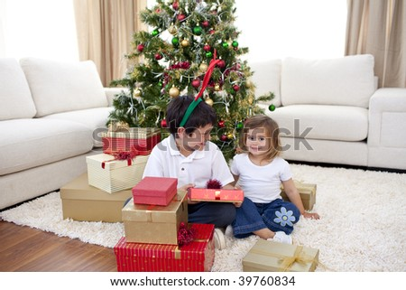 Happy children celebrating Christmas with presents at home