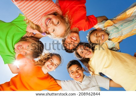 Happy children close in circle on sky background - stock photo