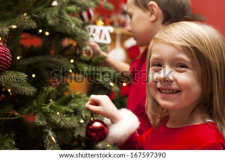 Happy children decorating Christmas tree - stock photo