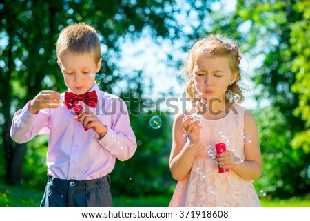 happy children doing soap bubbles outdoors - stock photo