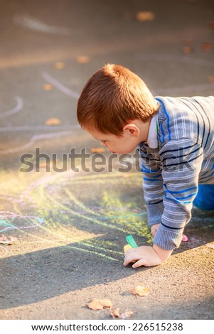 happy children draw with crayons on the pavement in the park - stock photo