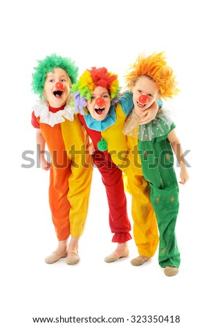 Happy children dressed up as colorful funny clowns - stock photo