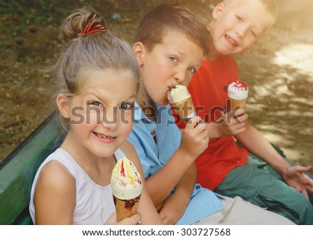Happy children eating ice cream outside - stock photo