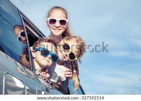 Happy children getting ready for road trip on a sunny day.  Concept of friendly family. - stock photo