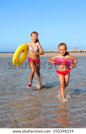 Happy children girls sisters with beach ring running on beach. - stock photo