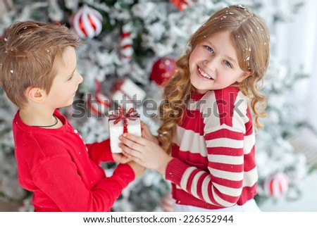 Happy children give a Christmas gift. Christmas concept.