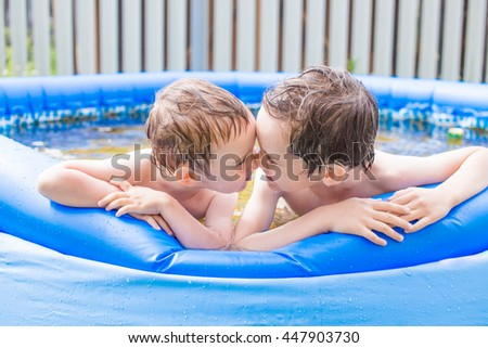 happy children having fun in the inflatable pool. funny kids rub noses and playing in the inflatable swimming pool in the garden. nose to nose, side view - stock photo
