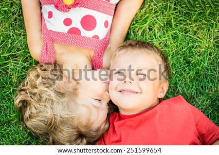 Happy children having fun outdoors. Kids playing in spring park. Boy and girl lying on green grass - stock photo