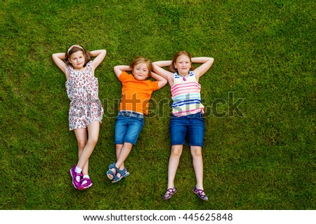 Happy children having fun outdoors. Kids playing in summer park. Little boy and two girls laying on green fresh grass