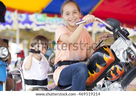 Happy children having fun riding on carnival carousel