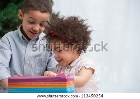 Happy children holding Christmas gifts and sitting on the floor - stock photo