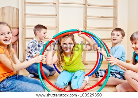 Happy children holding colorful hula hoops in gym - stock photo