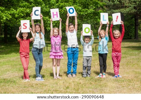 Happy children holding placecards with word school outdoors - stock photo