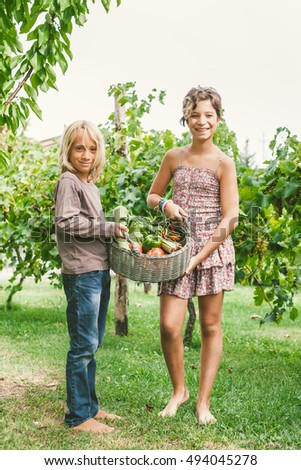Happy Children Holding Wicker Basket Full Of Fresh and Raw Vegetables