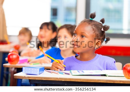 Happy children in a multi ethnic elementary classroom. - stock photo