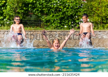 Happy children in a swimming pool. Sunny day - stock photo