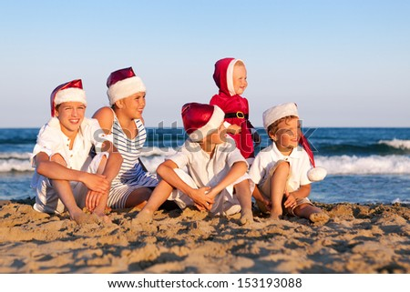 HAppy Children in santa claus hat  are sitting on beach, outdoor - stock photo